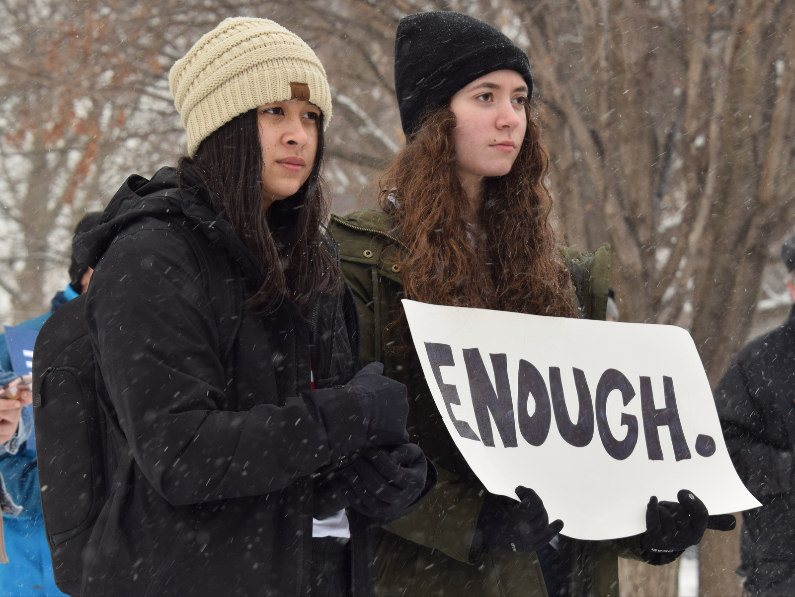 Two Students hold a sign that says enough at a March for Our Lives event